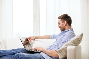 Man at home on couch using his laptop