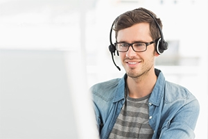 Man at computer with headset